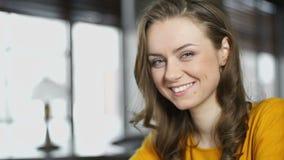 Mujer sonriente con la taza de caf? que mira la c?mara, estudio del servicio del restaurante almacen de video