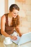 Mujer sonriente con la taza de café que trabaja en la computadora portátil Imagenes de archivo