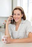 Mujer sonriente con la taza de café usando el teléfono móvil en cocina Fotos de archivo