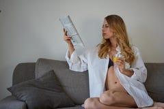 Mujer sonriente con la taza de revista de la lectura del café Fotografía de archivo libre de regalías