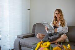 Mujer sonriente con la taza de revista de la lectura del café Fotografía de archivo