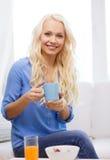 Mujer sonriente con la taza de té que desayuna Foto de archivo