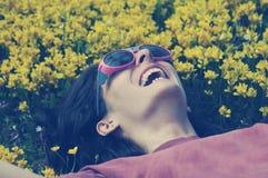 Mujer sonriente con las gafas de sol que ponen en un prado por completo con yello imagen de archivo libre de regalías
