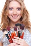 Mujer sonriente con las herramientas del maquillaje Imagen de archivo libre de regalías