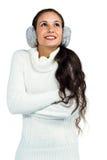 Mujer sonriente con las orejeras que cruzan los brazos y que miran para arriba Foto de archivo libre de regalías