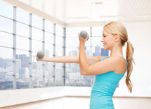 Mujer sonriente con las pesas de gimnasia que doblan bíceps en gimnasio Imágenes de archivo libres de regalías