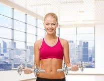 Mujer sonriente con las pesas de gimnasia que doblan bíceps en gimnasio Fotografía de archivo libre de regalías