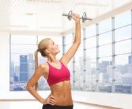Mujer sonriente con las pesas de gimnasia que doblan bíceps en gimnasio Fotos de archivo