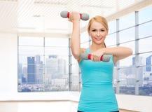 Mujer sonriente con las pesas de gimnasia que doblan bíceps en gimnasio Imagen de archivo