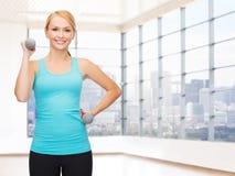 Mujer sonriente con las pesas de gimnasia que doblan bíceps en gimnasio Imagenes de archivo