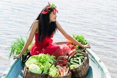 Mujer sonriente con las verduras en un barco Imagen de archivo