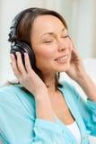 Mujer sonriente con los auriculares en casa Foto de archivo libre de regalías
