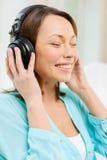 Mujer sonriente con los auriculares en casa Imagen de archivo