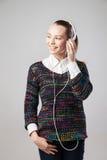 Mujer sonriente con los auriculares que escucha la música Fotos de archivo libres de regalías