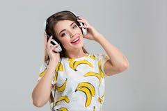 Mujer sonriente con los auriculares que miran la cámara Fotografía de archivo