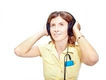 Mujer sonriente con los auriculares sobre blanco Fotografía de archivo