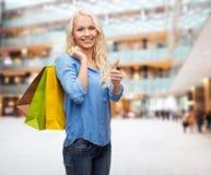 Mujer sonriente con los bolsos de compras que muestran los pulgares para arriba Fotos de archivo libres de regalías