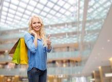 Mujer sonriente con los bolsos de compras que muestran los pulgares para arriba Foto de archivo
