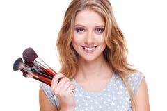 Mujer sonriente con los cepillos del maquillaje Foto de archivo