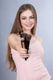Mujer sonriente con los cepillos del maquillaje Fotografía de archivo libre de regalías