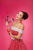 Mujer sonriente con los cepillos del maquillaje Ella se está colocando fotografía de archivo