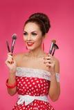 Mujer sonriente con los cepillos del maquillaje Ella se está colocando imagen de archivo