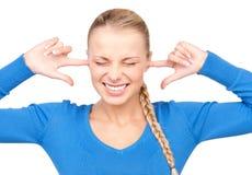 Mujer sonriente con los dedos en oídos Imagen de archivo