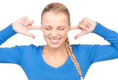 Mujer sonriente con los dedos en oídos Fotografía de archivo libre de regalías