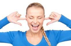 Mujer sonriente con los dedos en oídos Imagen de archivo libre de regalías