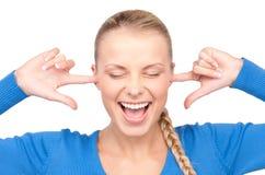 Mujer sonriente con los dedos en oídos Fotos de archivo