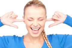 Mujer sonriente con los dedos en oídos Fotografía de archivo
