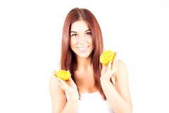 Mujer sonriente con los dientes blancos que sostienen dos halfs de naranja Fotografía de archivo