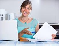 Mujer sonriente con los documentos en la cocina Foto de archivo