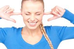 Mujer sonriente con los fingeres en oídos Fotografía de archivo libre de regalías
