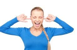 Mujer sonriente con los fingeres en oídos Imagen de archivo