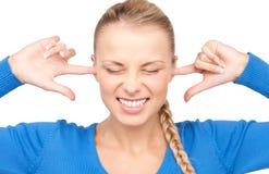 Mujer sonriente con los fingeres en oídos Imagenes de archivo