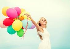 Mujer sonriente con los globos coloridos afuera Imagen de archivo