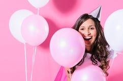 Mujer sonriente con los globos rosados y blancos Foto de archivo