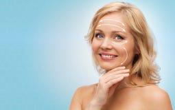 Mujer sonriente con los hombros desnudos que tocan la cara Imagen de archivo libre de regalías