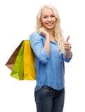 Mujer sonriente con los panieres que muestran los pulgares para arriba Imagen de archivo libre de regalías