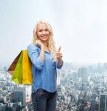 Mujer sonriente con los panieres que muestran los pulgares para arriba Fotos de archivo libres de regalías
