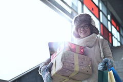 Mujer sonriente con los regalos apilados y la ventana que hace una pausa que hace compras durante invierno Fotos de archivo libres de regalías