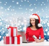 Mujer sonriente con los regalos, el ordenador portátil y la tarjeta de crédito Imagen de archivo