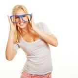 Mujer sonriente con los vidrios del empollón encendido Imagenes de archivo