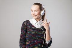 Mujer sonriente con música que escucha de los auriculares Fotos de archivo libres de regalías