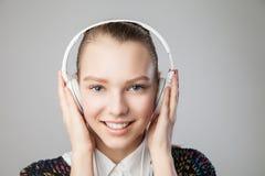 Mujer sonriente con música que escucha de los auriculares Foto de archivo libre de regalías