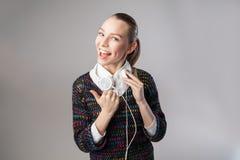 Mujer sonriente con música que escucha de los auriculares Fotos de archivo