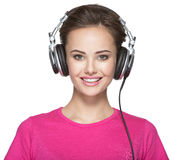 Mujer sonriente con música que escucha de los auriculares Imagen de archivo libre de regalías