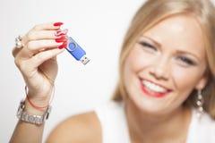 Mujer sonriente con memoria USB en manos Imagenes de archivo