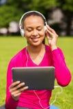 Mujer sonriente con PC de la tableta al aire libre Imagen de archivo